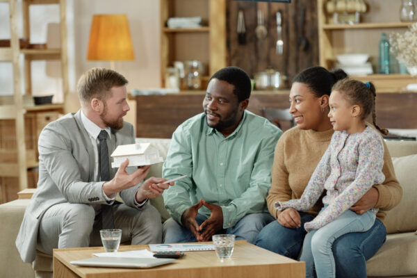 Bearded elegant adviser with mockup house consulting adult ethnic couple with kid on new real estate
